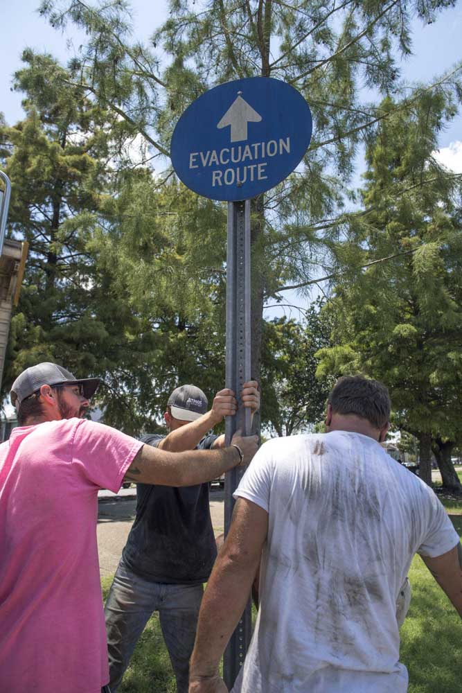 Davie Shoring crews try to move a hurricane evacuation sign as they clear the way for an 1895 shotgun house that they were moving in New Orleans on Wednesday, July 24, 2019.