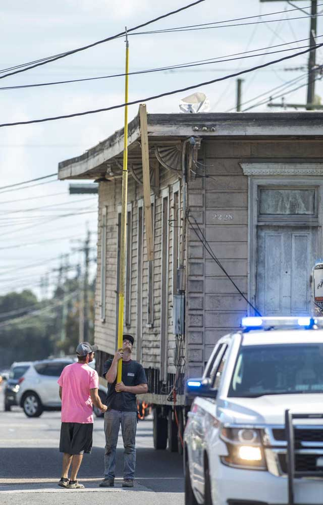 Davie Shoring crews lift power lines over an 1895 shotgun house as it is slowly moved down Almonaster Ave. in New Orleans on Wednesday, July 24, 2019.