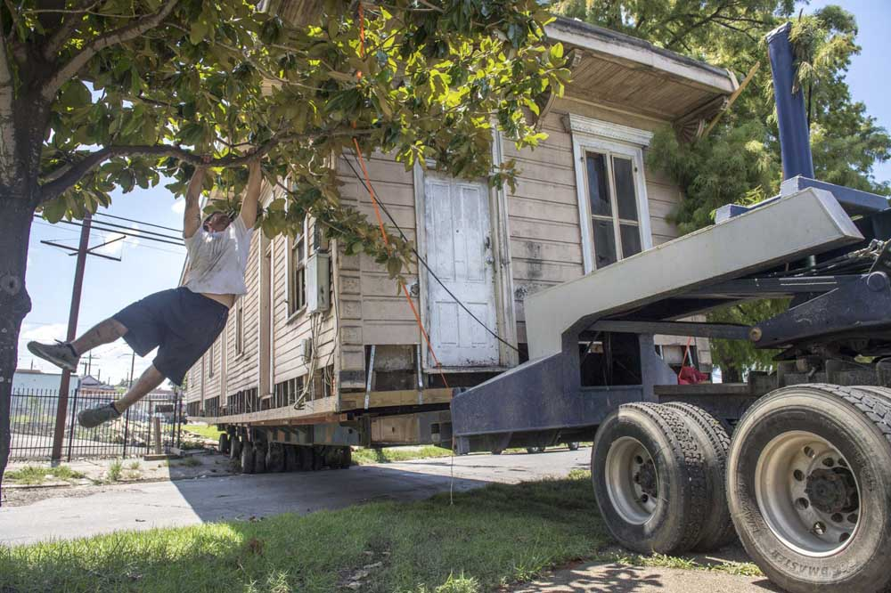 A Davie Shoring crewman, left, jumps into a tree to move branches out of the way as an 1895 shotgun house is moved from Martin Luther King Blvd. in New Orleans on Wednesday, July 24, 2019.